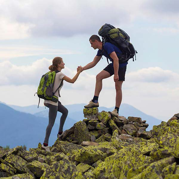Man helping a woman during hiking