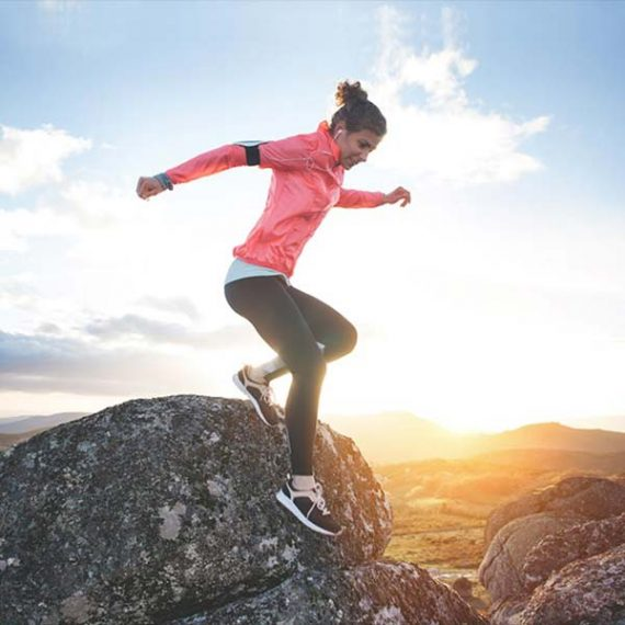 Female runner jumping down from a rock