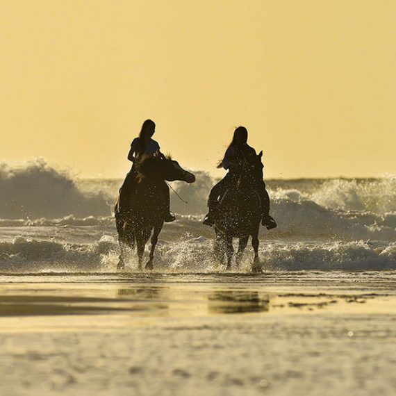 Two women on horses in the sea